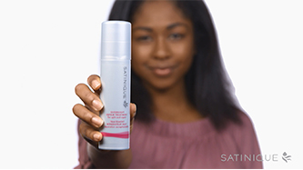 Background image showing woman holding Satinique™ Overnight Repair Treatment.