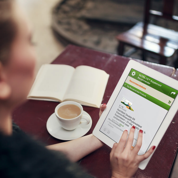 Woman looking at a tablet with results from Nutrilite Supplement Recommender displayed while sitting at a table with a cup of coffee and an open book.