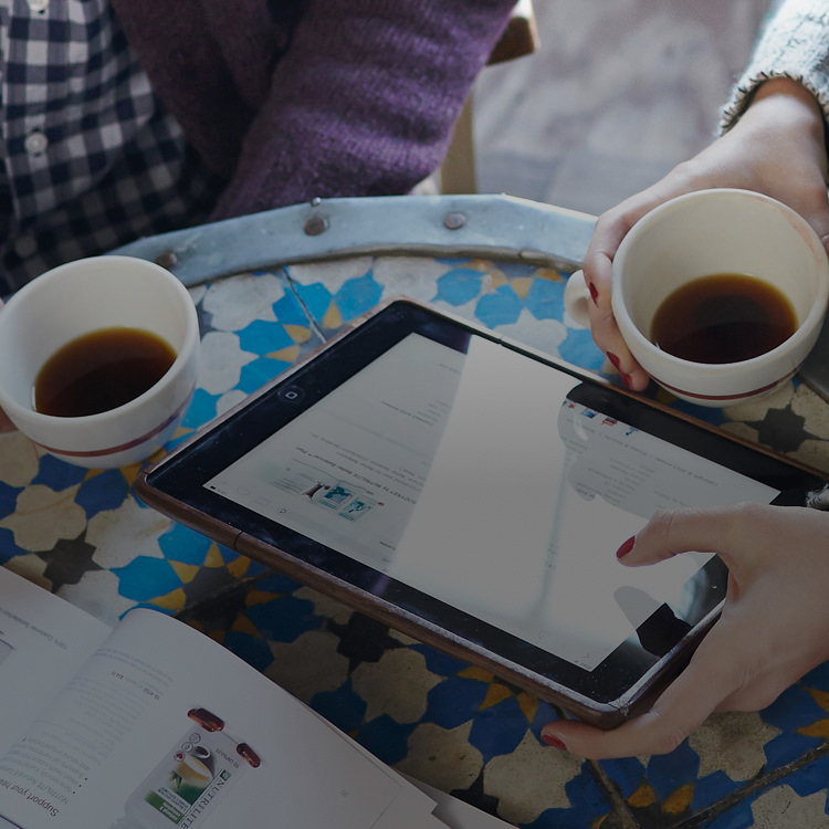 Man and woman having coffee, looking at Amway website on a tablet.