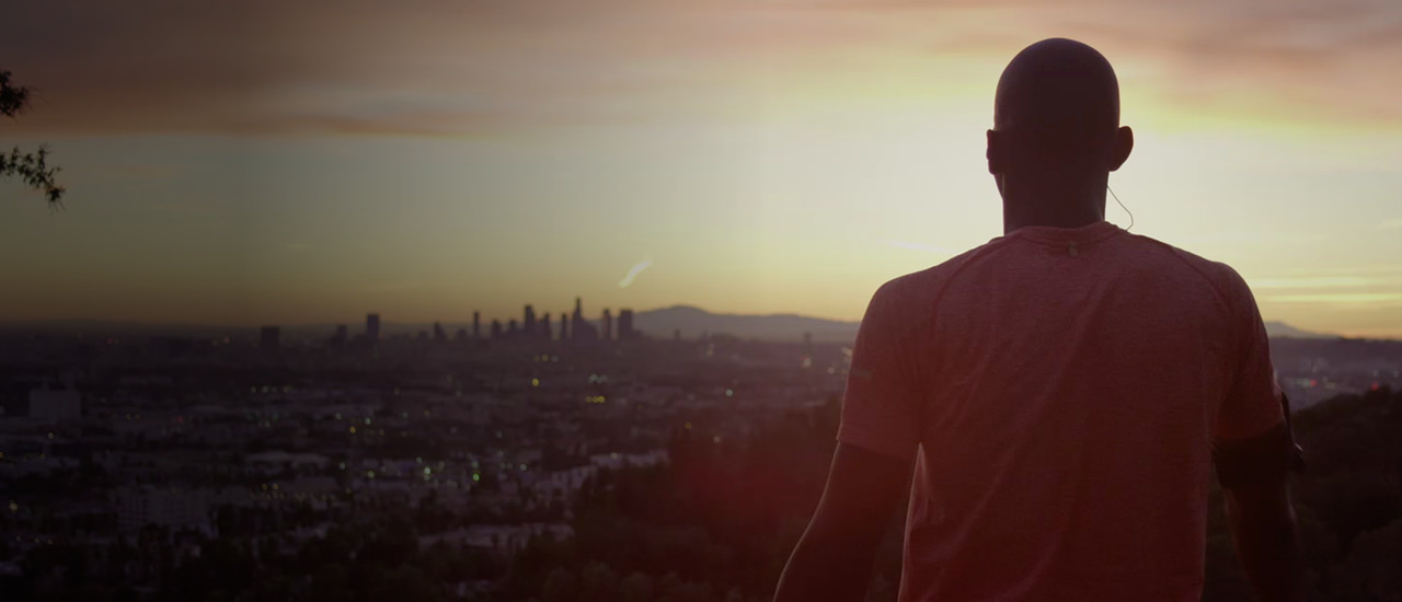 Man standing on a hilltop overlooking a city at sunrise.
