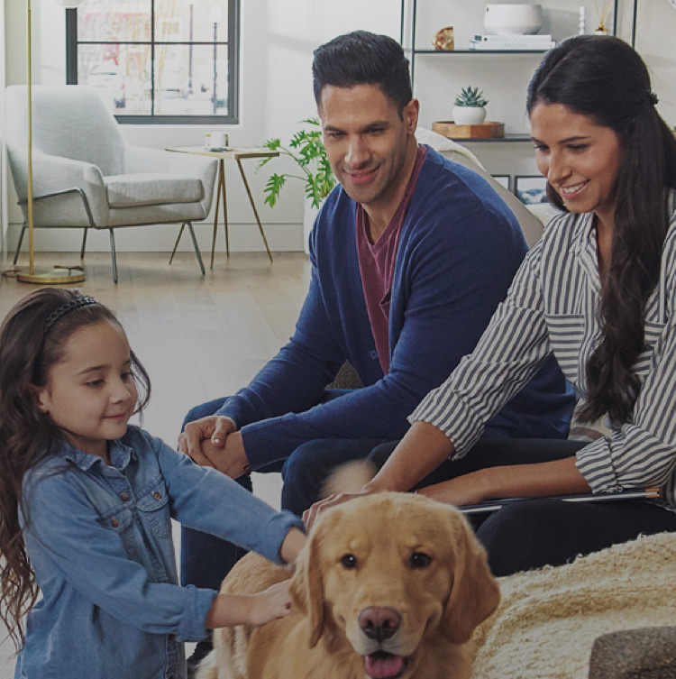 Family and their dog sitting in a living room with Atmosphere Sky™ air treatment system.