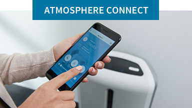 Atmosphere™ Connect: Hand using Atmosphere™ Connect App on a smartphone with Atmosphere Sky™ air treatment system in background.