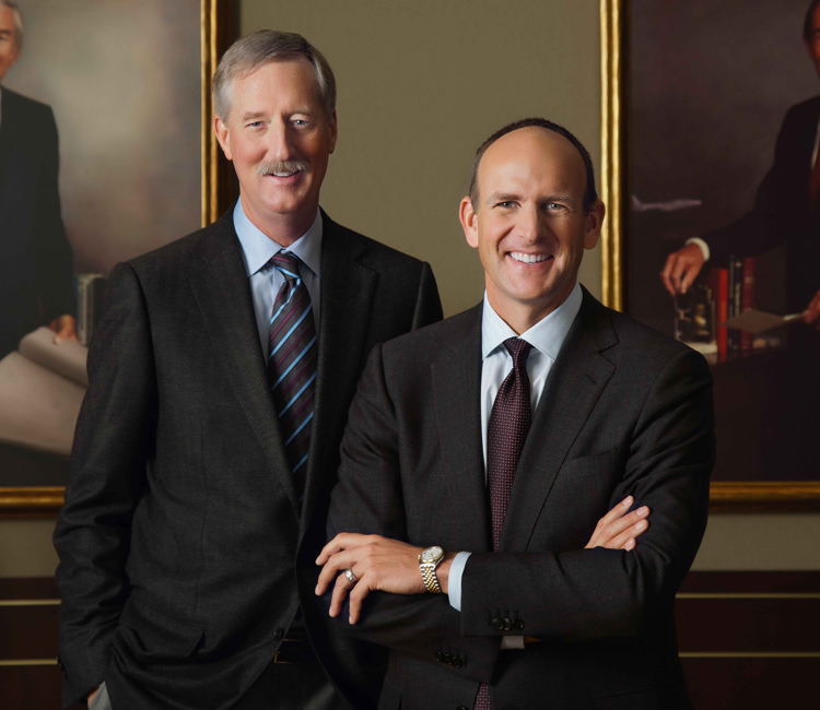 Steve Van Andel and Doug DeVos standing in front of painted portraits of Jay Van Andel and Rich DeVos.