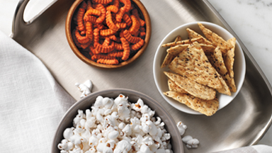 BodyKey™ Snacks: Tasty and fulfilling. Background image shows BodyKey™ Snacks in bowls on a silver metal plater.