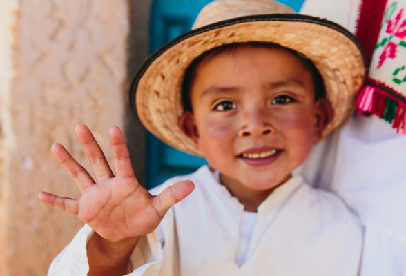 Little boy smiling holding his right hand up to show five fingers for the Nutrilite Power of 5 program.