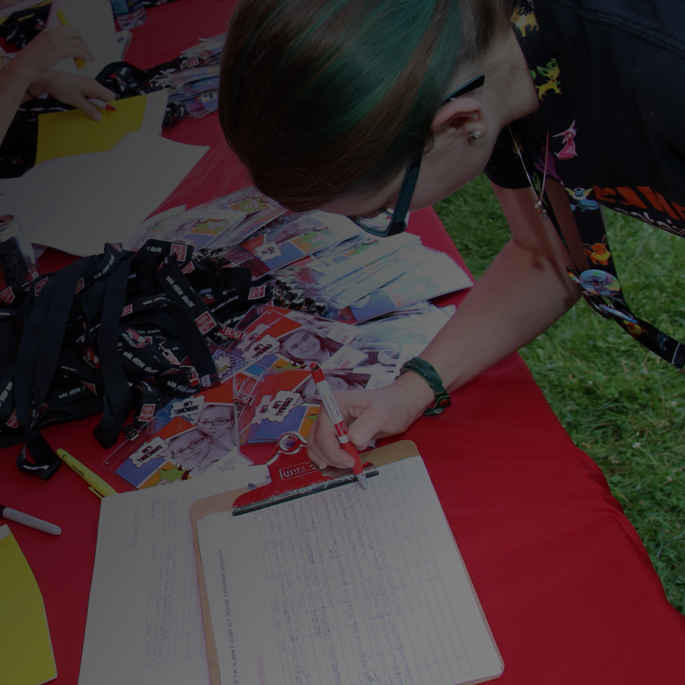 Volunteer filling out a form at a sign in table for an Easterseals™ event.