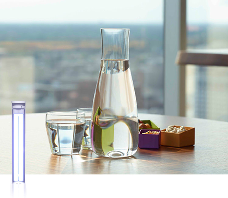 A pitcher and two glasses filled with water on a table with snacks. Ultraviolet light bulb shown next to the image.