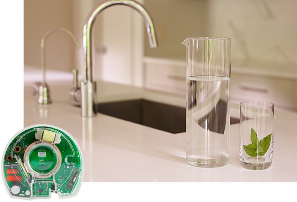A kitchen counter with an under the sink eSpring™ water purifier installed (not shown). A pitcher full of water and an glass with mint inside sits on the counter.