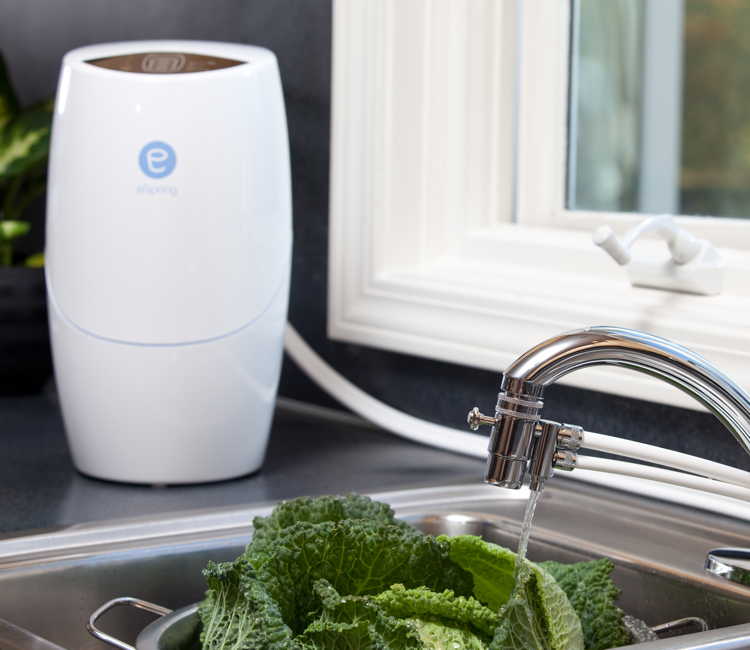 Above counter eSpring™ unit hooked up to a kitchen sink faucet to wash vegetables.