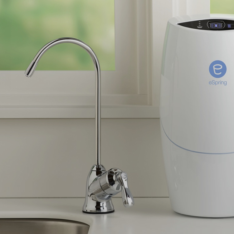 eSpring™ above the counter unit shown on a countertop with chrome water faucet to dispense filtered water.