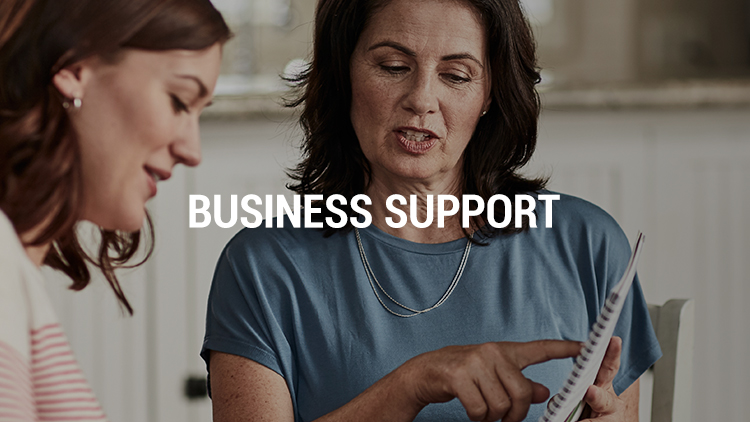 Business Support. Background image shows two dark haired women discussing business around a table.