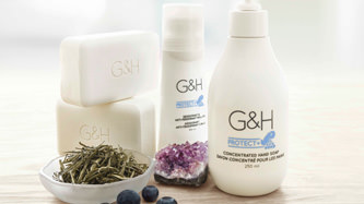 G&H Protect+™: Clean & protect your skin. Background image shows G&H Protect+™ Concentrated Hand Soap, G&H Protect+™ Bar Soap, G&H Protect+™ Deodorant & Anti-Perspirant Roll-On, surrounded by dried white tea leaves, bilberries and an amethyst crystal.