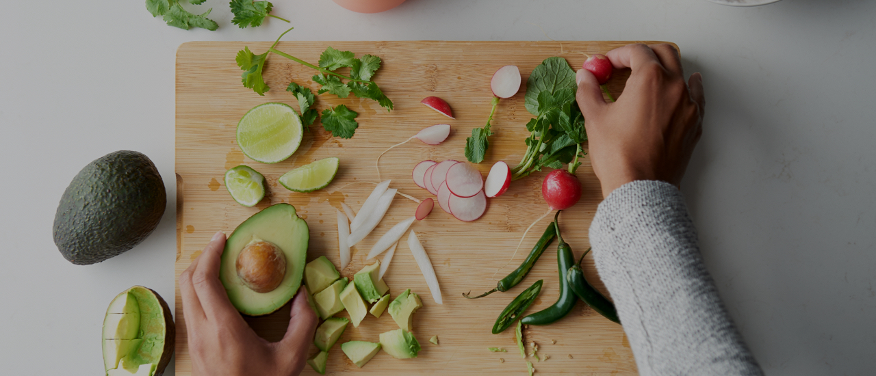Woman's hands slicing fruits and vegetables on a wooden cutting board: avocado, lime, cilantro, radishes, onion, peppers.