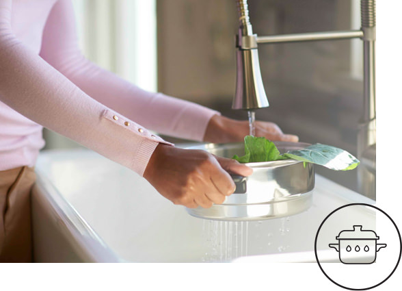 Woman washing vegetables using a iCook™ Steamer Insert as colander. iCook™ Vitalok™ icon showing a covered pot holding in liquid.