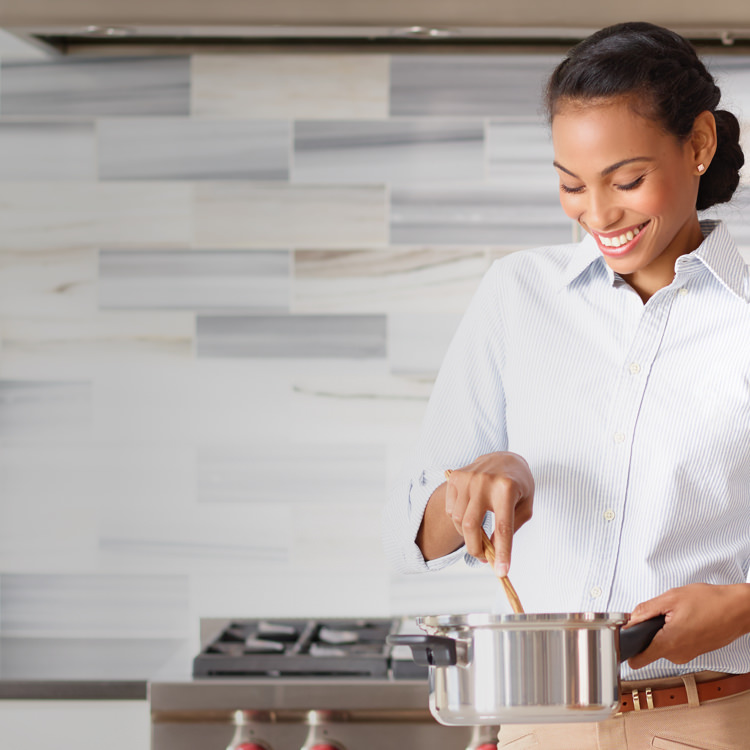 Smiling woman cooking with iCook™ cookware in a kitchen with a gas stove.
