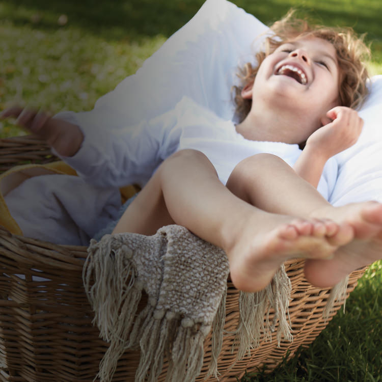Young girl laughing while sitting in a clean pile of laundry in a wicker basket.