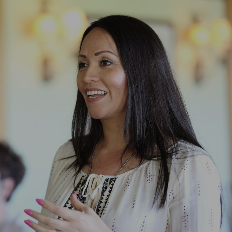 Dark haired woman speaking at a presentation.