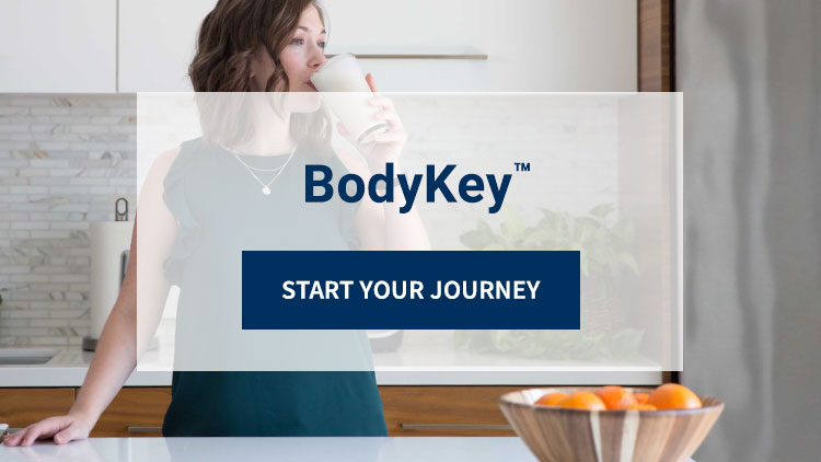 BodyKey™ Weight-Loss Program: There's so much to gain from losing weight! Start Your Journey. Background image shows woman enjoying a BodyKey shake in the kitchen.