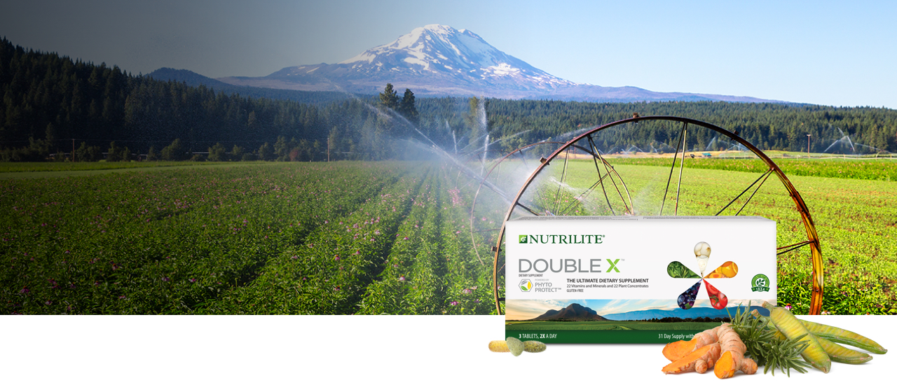 Nutrilite™ Double X™ Multivitamin shown with turmeric, rosemary and fava d'anta. Background image shows Amway certified organic farm in Trout Lake, Washington.