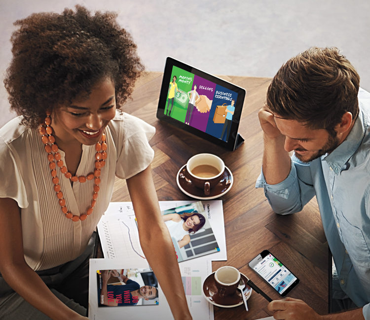 Man and woman meeting over coffee, discussing Amway Education on a tablet. Amway App shown on smartphone. Amway App logo.