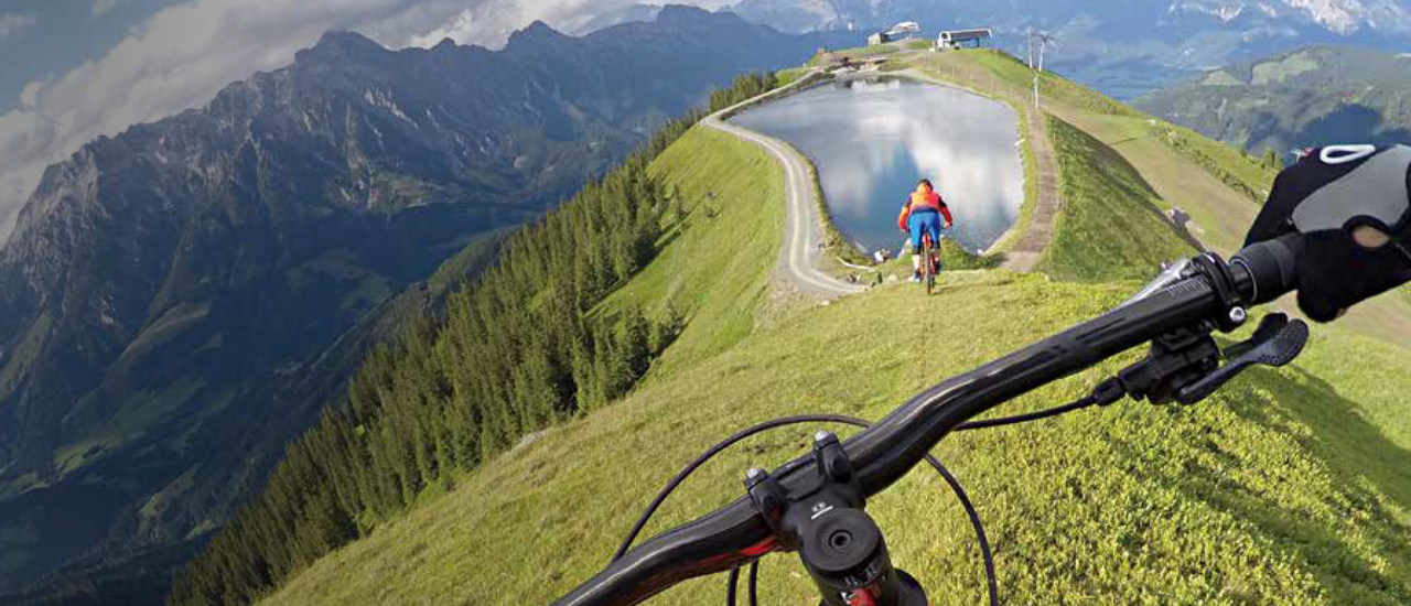 Two mountain bikers on the ridge of a grass covered mountain with a lake on top of it.